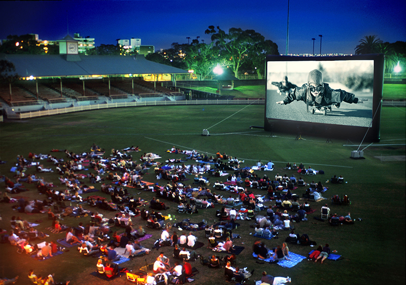 A large crowd gathered at an outdoor movie at night.