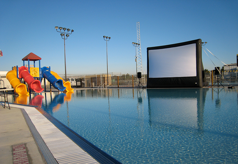 A large movie screen at an empty pool.