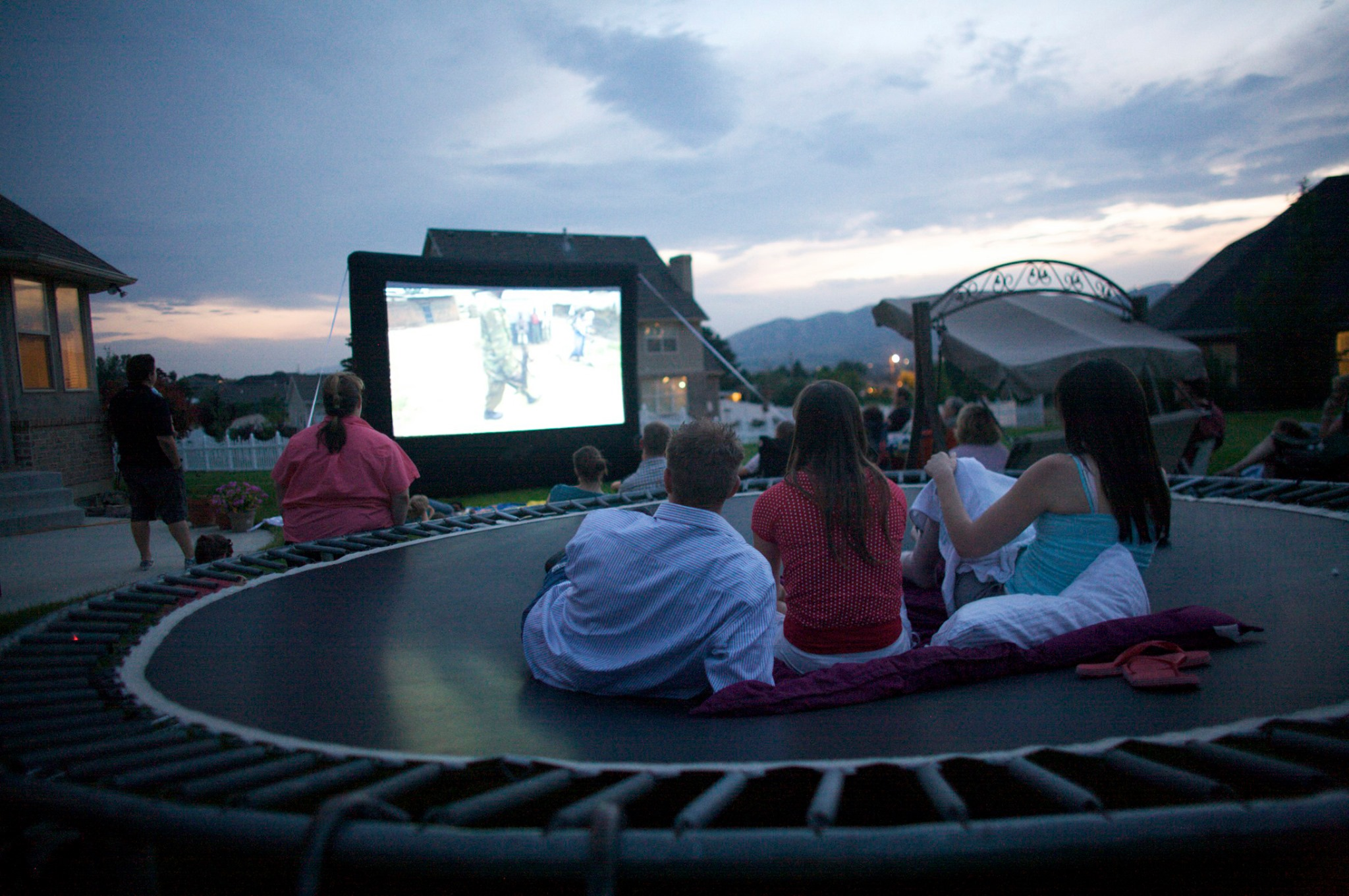 3 people laying outside on a trampoline watching a movie on a big screen.